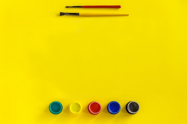 Malerpinsel und gouache auf gelbem aquarellpapier