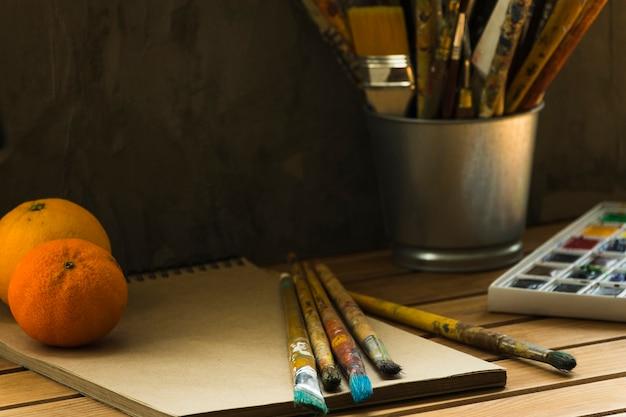 Malerwerkzeuge und -orangen auf einer tabelle