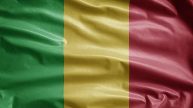 Malische flagge weht im wind. nahaufnahme von mali-banner, die glatte seide weht