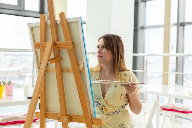 Malkunstunterricht. zeichenkurse. fähigkeiten fantasie und inspiration. charmantes studentenmädchen, das bild auf staffelei schafft.