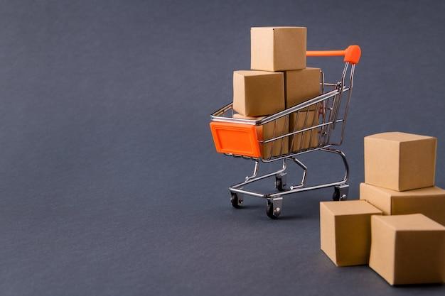 Mall-schubkarren mit sachen in papierkisten, die die bestellung nach hause liefern