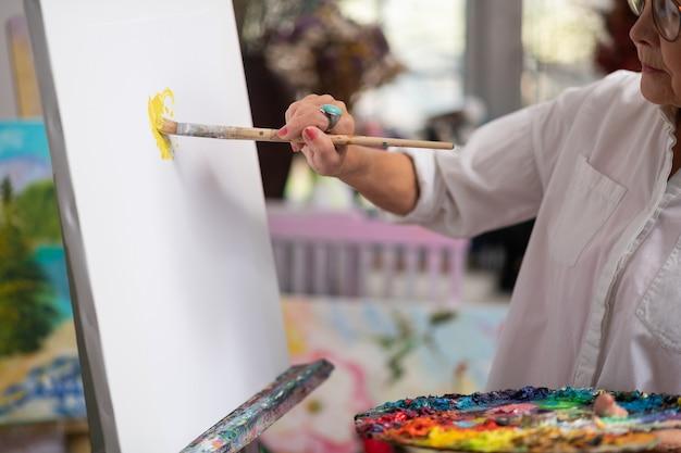 Malpinsel halten. talentierte kreative frau, die malpinsel hält und mit gouache malt