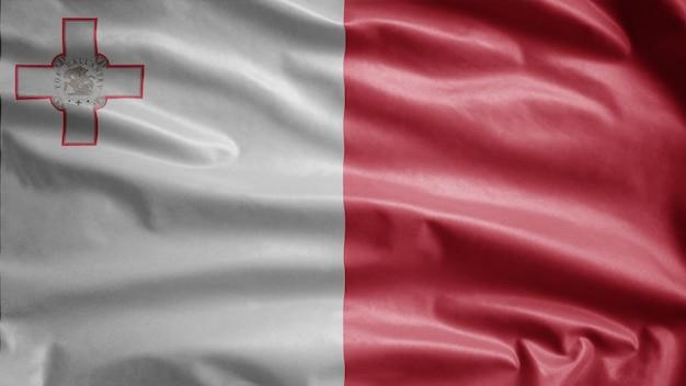 Maltesische flagge weht im wind. nahaufnahme von malta banner weht weiche seide. stoff textur fähnrich hintergrund.