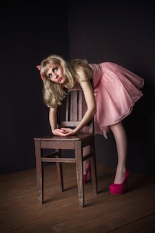 Malvina mädchen im rosafarbenen kleid, das auf dem stuhl liegt