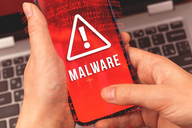 Malware-konzept mit person, die smartphone verwendet, hintergrund des laptops
