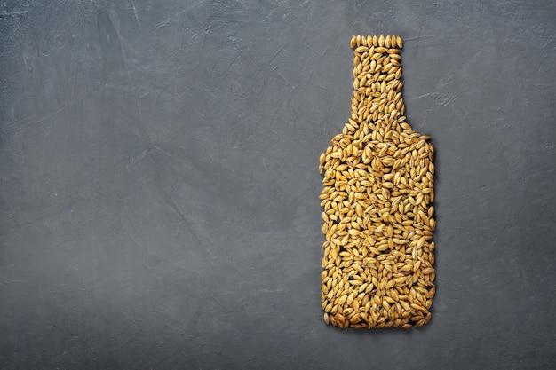 Malzkörner werden als bierflasche auf grauem betonhintergrund ausgelegt.