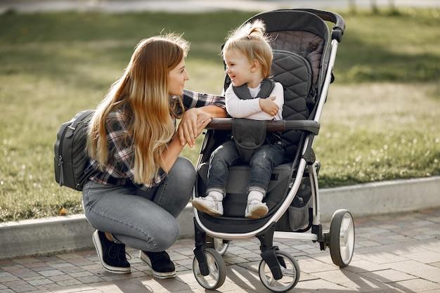 Mama auf der stadtstraße. frau mit ihrem kleinkind sitzt in einem kinderwagen. familienkonzept.