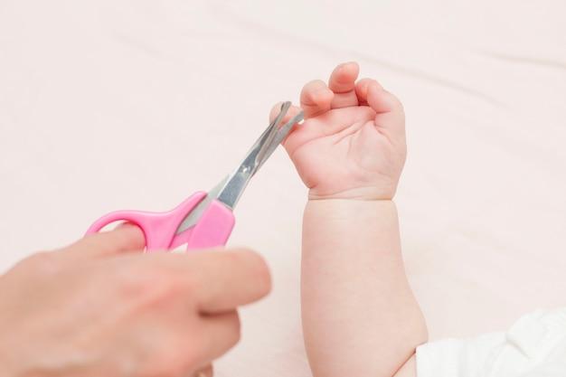 Mama bekommt eine maniküre mit einer nagelschere und schneidet ihrem süßen baby die nägel, während sie auf dem bett liegt. das konzept der kinderbetreuung.