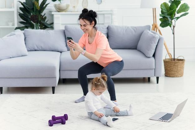 Mama benutzt das smartphone, während sie morgens zu hause trainiert. mutter macht fitnessübungen, gesundes lebensstilkonzept.