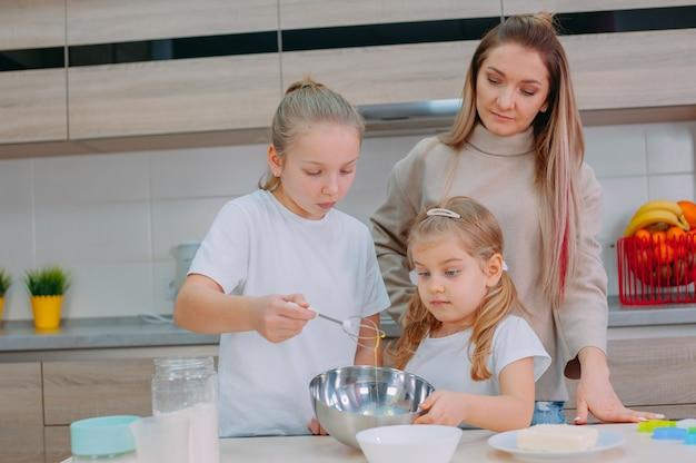 Mama bringt ihren töchtern bei, in der küche teig zu kochen.