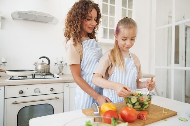 Mama bringt ihrer jugendlichen tochter bei, gemüsesalat in der küche zu kochen