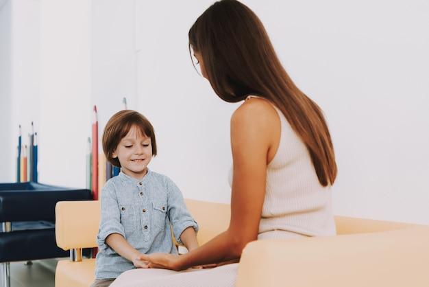 Mama, die mit glücklichem kind in der klinik-halle spielt.
