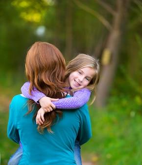 Mama, die tochterkindermädchen in ihrem lächeln der hinteren ansicht der arme hält
