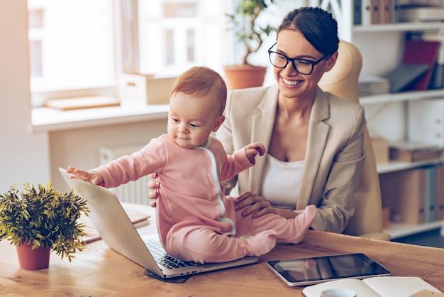 Mama es ist zeit für eine pause! fröhliche junge schöne geschäftsfrau, die ihr baby mit einem lächeln betrachtet, während sie an ihrem arbeitsplatz sitzt