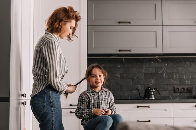Mama flechtet ihre kleinen tochter zöpfe. porträt der frau und der frau in der küche.