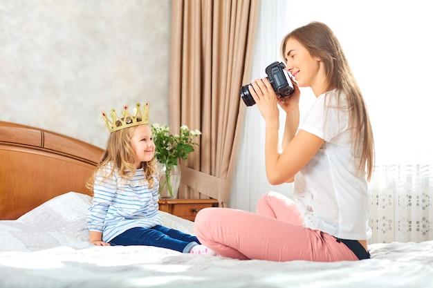 Mama fotografiert ihr kind in einem raum am fenster