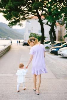 Mama führt ihre kleine tochter an der hand den damm der stadt perast entlang, vorbei an autos und bäumen