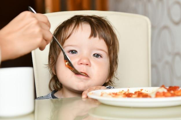 Mama füttert das baby mit einer gabel Premium Fotos