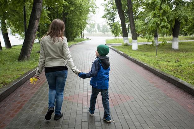 Mama geht mit ihrem sohn im sommer spazieren, geht mit familie, familientraditionen, liebe und verständnis