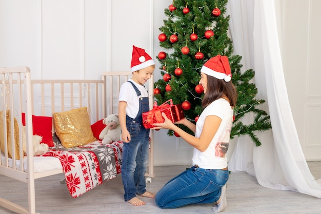 Mama gibt einem kind ein geschenk in einer großen roten schachtel neben dem weihnachtsbaum