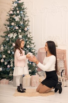 Mama gibt ihrer geliebten tochter eine schachtel mit einem weihnachtsgeschenk.
