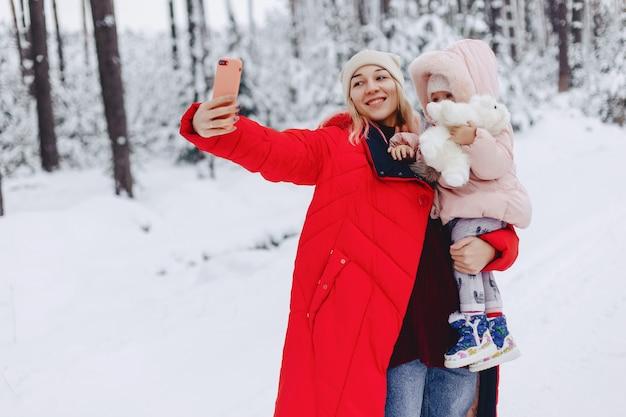 Mama hält das baby in den armen und macht das selfie im verschneiten gebiet