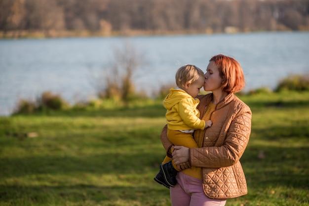 Mama hält den sohn eines kleinkindes in den armen und küsst ihn auf die stirn