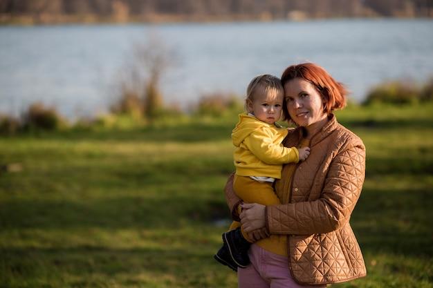 Mama hält den sohn eines kleinkindes vor dem hintergrund des herbstwaldes und des sees in den armen