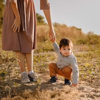 Mama hält ihr einjähriges baby an der hand für einen spaziergang im park am fluss.
