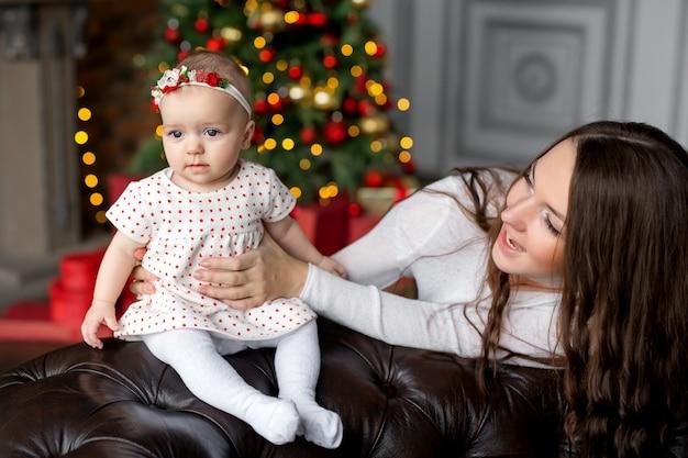 Mama hält kleine tochter fröhlich lachend am weihnachtsbaum mit girlande und buntem bokeh