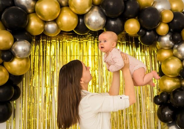 Mama hielt ihre kleine tochter mit luftballons auf festlichen vorhängen hoch