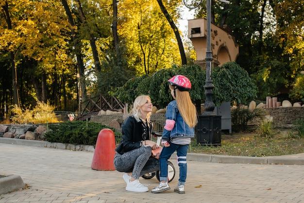 Mama hilft dabei, die ausrüstung und den helm ihrer kleinen tochter für eine segway-fahrt im park anzuziehen