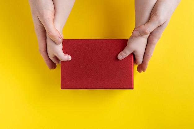 Mama hilft dem kind, box zu nehmen. mama und baby halten pappkarton. speicherplatz kopieren. attrappe, lehrmodell, simulation.