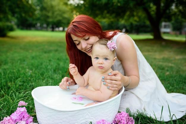 Mama hilft ihrer kleinen einjährigen tochter beim baden im badezimmer. gefilmt in einem park im freien in der natur.