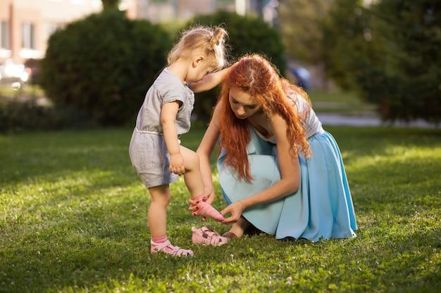 Mama hilft ihrer tochter, schuhe zu tragen