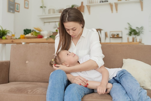 Mama hört auf die probleme ihrer kleinen töchter, umarmt sie und tröstet sie