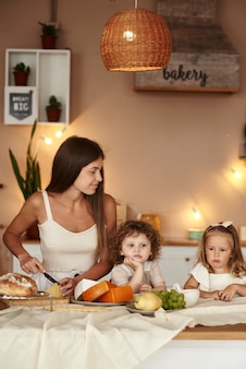 Mama in der küche bereitet ihren kindern ein gesundes frühstück zu.