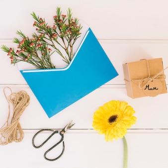 Mama-inschrift mit geschenk, gerbera und umschlag