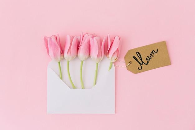 Mama-inschrift mit tulpen im umschlag