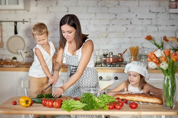 Mama kocht das mittagessen mit den kindern. eine frau bringt ihrer tochter bei, von ihrem sohn zu kochen. vegetarismus und gesunde natürliche ernährung