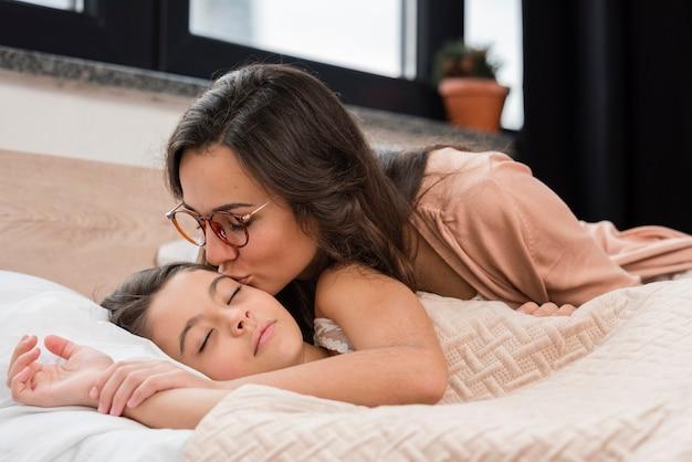 Mama küsst ihre tochter gute nacht