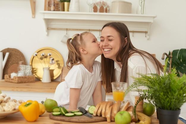 Mama küsst ihre tochter in der küche. glückliche familie zu hause. gesundes lebenskonzept der familie.