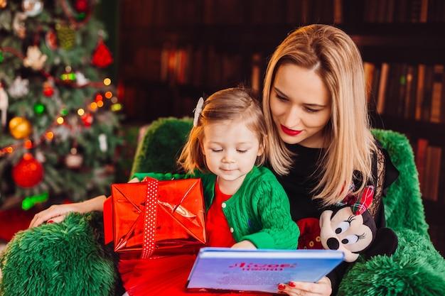 Mama liest ein buch mit ihrer kleinen tochter, die im stuhl vor weihnachtsbaum sitzt
