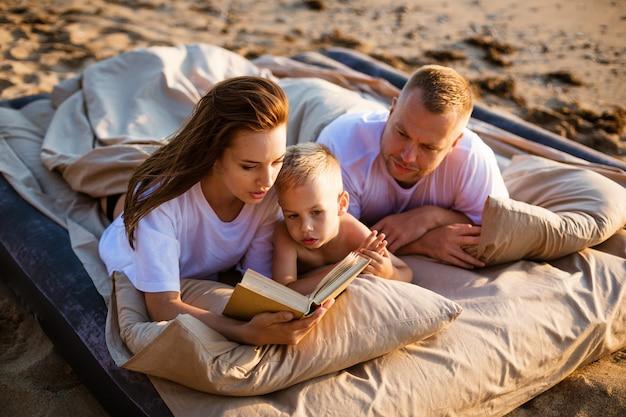 Mama liest ihrem sohn ein buch vor, während sie auf dem bett liegt