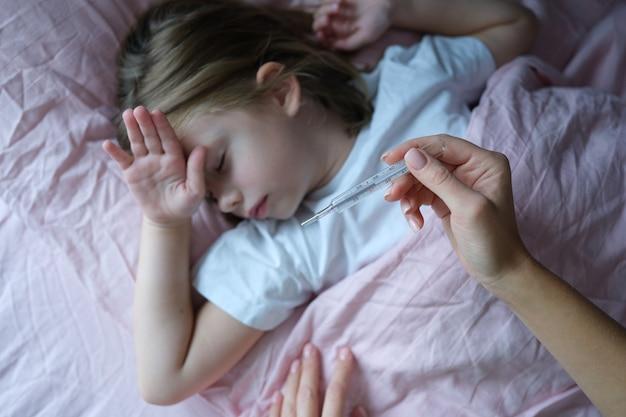 Mama misst die körpertemperatur eines kleinen kranken mädchens, das im bett liegt. vorübergehender anstieg der körpertemperatur bei einem kind