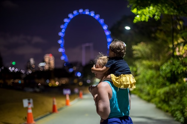 Mama mit baby auf den schultern im abendlichen stadtpark vor dem hintergrund des riesenrads