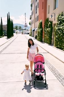 Mama mit einem kleinen mädchen rollt einen kinderwagen durch die stadtstraße