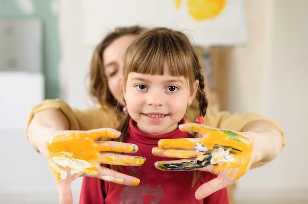 Mama mit ihrer tochter streckt ihre hände aus, mit farbe befleckt