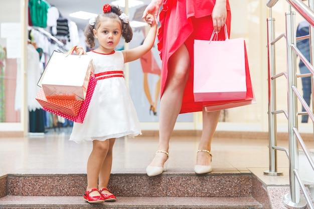 Mama mit kleiner tochter in kleidern im einkaufszentrum mit bunten taschen