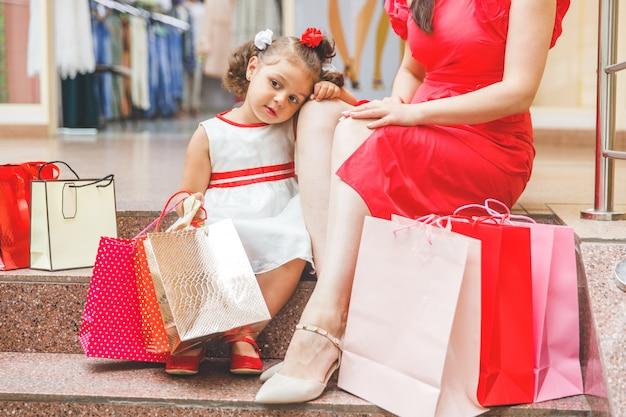 Mama mit kleiner tochter in kleidern sitzt mit bunten taschen auf den stufen im einkaufszentrum
